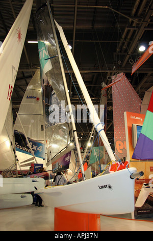 laser dingy at the london boat show with loads of sails in the background - Stock Image
