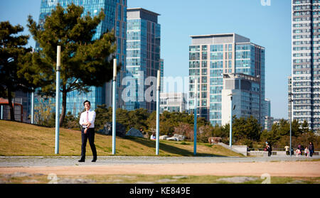 Businessman talking a walk at park - Stock Image