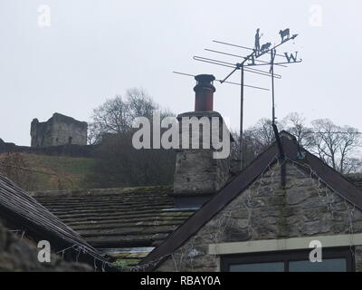 Cottage rooftops, chimneys and TV aerials of the Derbyshire Peak District village of Castleton, overlooked by Peveril Castle on the hillside above - Stock Image