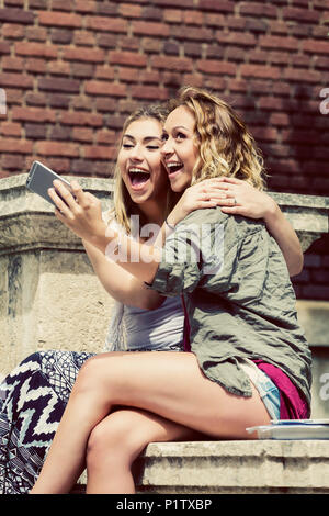 Two female university students sitting together on the campus, being silly and taking a self-portrait with their smart phone - Stock Image