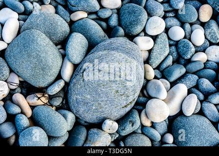 Round stones on a beach - Stock Image