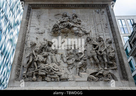One side of the base of The Monument to the Great Fire of London decorated with a carving. - Stock Image