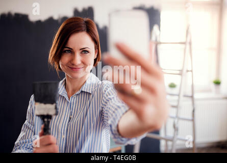 A portrait of young creative woman with smartphone painting wall black, taking selfie. A startup of small business. - Stock Image