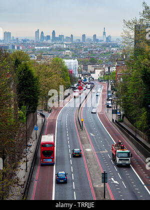 London, England, UK - April 13, 2011: Traffic flows along the Archway Road in the North London suburbs, with the skyline of the City of London busines - Stock Image