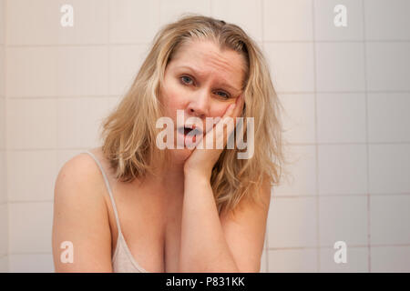 Woman sits in bathroom with hand on face looking sleepy, big yawn - Stock Image