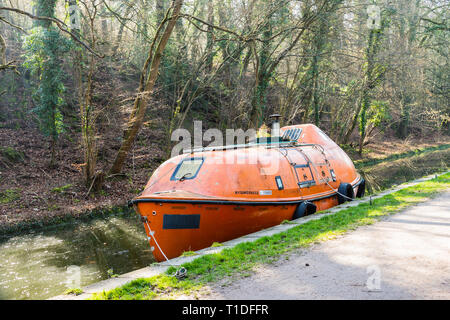 A fully enclosed freefall lifeboat has been converted into a houseboat and is seen moored on the Kennet and Avon canal - Stock Image