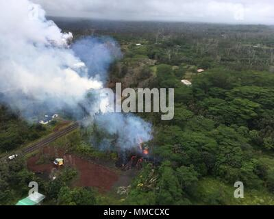 Leilani Estates, Hawaii. May 9, 2018. Aerial view of lava and steam spewing from fissure 15 near Pohoiki Road caused by the Kilauea volcano eruption May 9, 2018 in Leilani Estates, Hawaii. The recent eruption continues destroying homes, forcing evacuations and spewing lava and poison gas on the Big Island of Hawaii. Credit: Planetpix/Alamy Live News - Stock Image