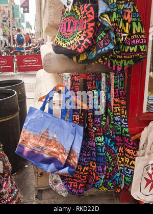 Colourful souvenir bags wit pictures and text to state that they are bought in Malta, on display in a souvenir shop in the centre of Valetta - Stock Image