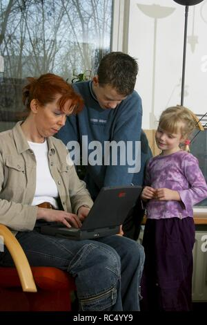 2003: Mother and 2 children curious looking at laptop on lap. - Stock Image