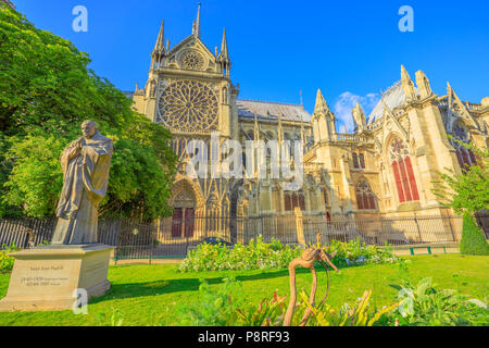 Pope John Paul II statue on side of church Notre Dame of Paris, France. Gothic architecture of Cathedral of Paris, Ile de la cite. Beautiful sunny day in the blue sky. - Stock Image