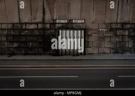 A dirty, old road under a bridge in central London - Stock Image