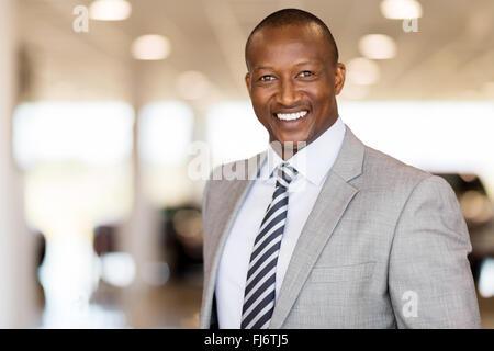 handsome African man working at car dealership - Stock Image