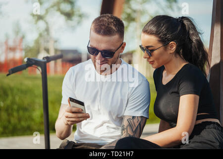Young man and woman sitting in park and looking at mobile phone screen. - Stock Image