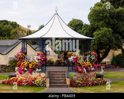 Summer bedding flowers bedeck the Victorian bandstand in Runnymede Gardens, Ilfracombe, Devon, UK - Stock Image
