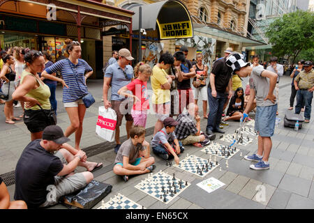 Young man in a pedestrianised street playing simultaneous chess  with several people, while others watch. Outdoor - Stock Image