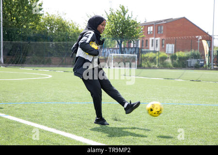 A Muslim woman holding a football shoots a ball at goal on an astroturf pitch - Stock Image