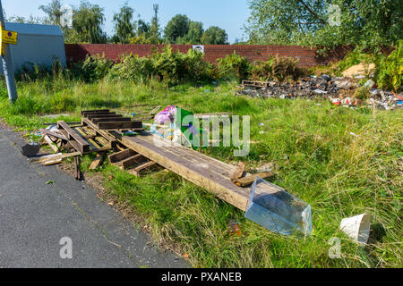 Fly tipping.  Waste dumped on a grass verge, New Viaduct Street, Beswick, Manchester, England, UK - Stock Image