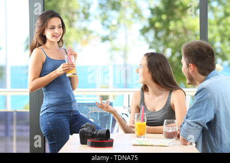 Happy friends talking enjoying holidays in a coffee shop or hotel on the beach - Stock Image