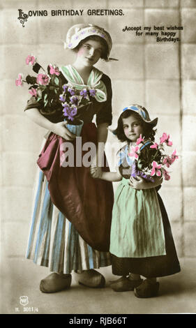 Birthday postcard, woman and girl in Dutch costume with flowers. - Stock Image