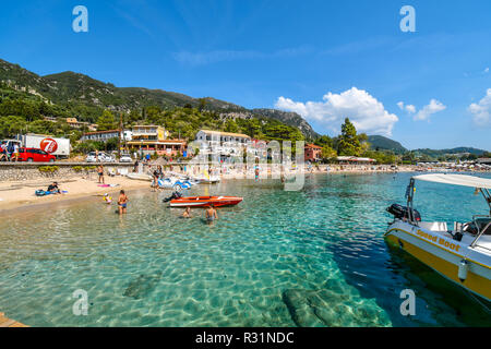 Tourists relax in the clear waters and on the sandy Palaiokastritsa beach on the Aegean island of Corfu, Greece. - Stock Image