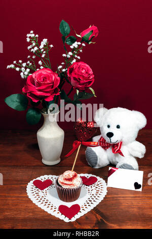 Beautiful pink roses in a vase accented with Baby's Breath flowers, heart shaped white dollie with a decorated cup cake with a heart on a pick. A whit - Stock Image