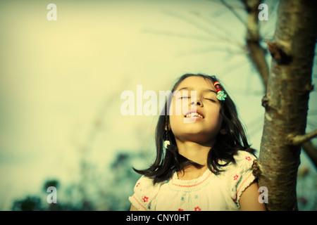 Girl basks in evening sun - Stock Image