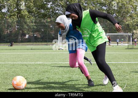 Muslim girls playing football on an astroturf training pitch. They are wearing hijabs (headscarves). - Stock Image