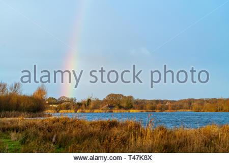 Rainbow over a lake in Dorset, near Wareham - Stock Image