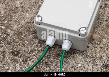 Weatherproof IP67 terminal box with cable glands and green CAT5e network cable - Stock Image