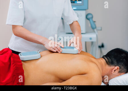 Magnetotherapy. Physical therapist placing magnets on patient's back. - Stock Image