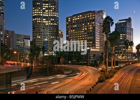 US 101, Harbor Freeway LA skyline, Dusk Los Angeles, California, USA Traffic moving CA LA city scape night - Stock Image