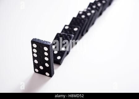 Dominoes - row of black dominoes on white - Stock Image