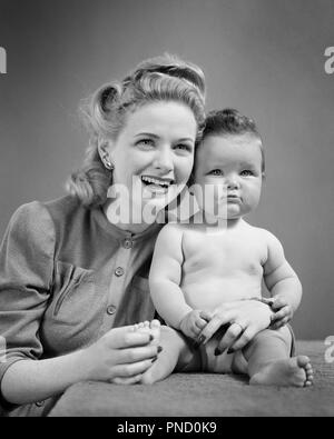 1940 SMILING BLONDE WOMAN MOTHER WITH POUTING BABY GIRL SITTING ON TABLE BOTH LOOKING AT CAMERA  - b9333 HAR001 HARS INFANT FEMALES HEALTHINESS HOME LIFE COPY SPACE FRIENDSHIP HALF-LENGTH LADIES DAUGHTERS PERSONS EXPRESSIONS B&W EYE CONTACT HAPPINESS BOTH POUTING UPDO VICTORY ROLLS GROWTH JUVENILES MOMS TOGETHERNESS YOUNG ADULT WOMAN BABY GIRL BLACK AND WHITE CAUCASIAN ETHNICITY HAR001 OLD FASHIONED - Stock Image