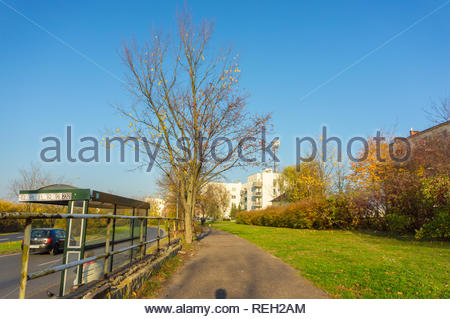 Poznan, Poland - November 7, 2018: Footpath and grass next to a road with bus stop. Located on the Inflacka street. - Stock Image