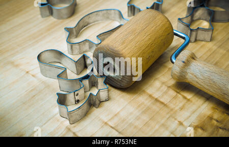 Kitchen utensils for preparing Xmas gingerbreads. Still life with a small rolling pin for dough. Metal cutters of various shapes on wood pastry board. - Stock Image
