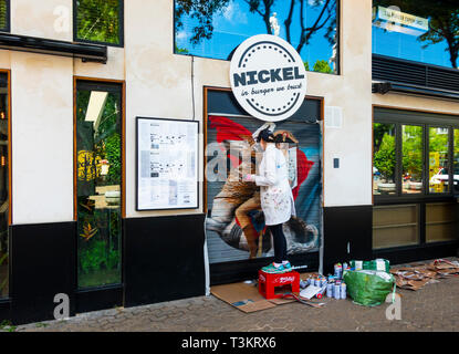 Woman artist painting a mural on a shutter of Nickel Burger, a restaurant in Seville - Stock Image
