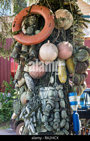 Old net floats decorate a tree along Hammer Slough in Petersburg, Mitkof Island, Alaska. Petersburg settled by Norwegian immigrant Peter Buschmann is known as Little Norway due to the high percentage of people of Scandinavian origin. - Stock Image