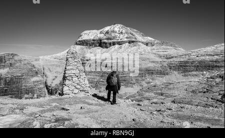 Tourist on the rock of the Sass Pordoi. View towards Piz Boe Mountain, Sella Group, Dolomites, Trentino province, Italy. Image in Black and white - Stock Image