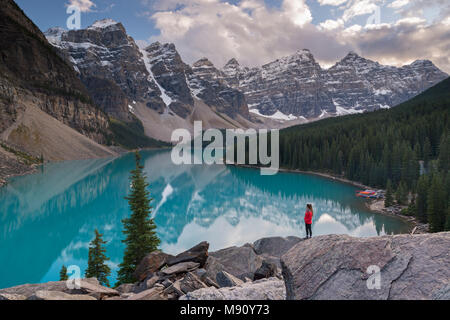 Woman looking over Moraine Lake from the Rockpile, Canadian Rockies, Banff National Park, Alberta, Canada. Autumn (September) 2017. - Stock Image