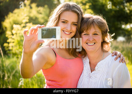 Teenage daughter and her senior mother are taking selfie photo with mobile phone - Stock Image