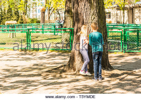 Poznan, Poland - April 18, 2019: Boy and girl hiding behind a tree playing hide and seek in the old zoo on a warm spring day. - Stock Image