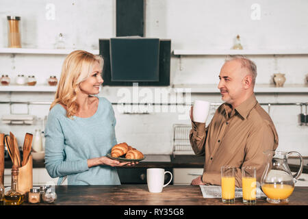 happy wife holding plate with croissants near husband with cup of drink - Stock Image