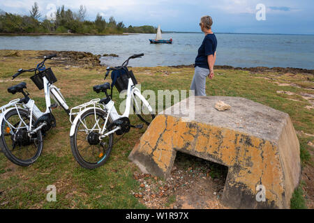 Female tourist with electric bikes watches traditional boat in the holiday village of Coleton, Bay of Pigs, Matanzas Province, Cuba - Stock Image