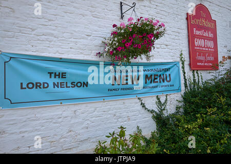 'Under New Management' banner sign on the outside exterior external wall of a British village pub public house, The Lord Nelson, Poppleton, York, UK. - Stock Image