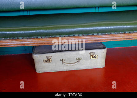 old suitcase under seat on red painted floor, norfolk, england - Stock Image