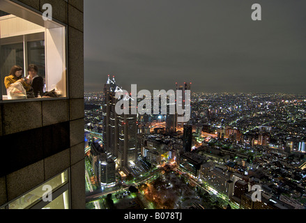 Japanese couple looking out over Tokyo by night. Illuminated cityscape from the 42nd floor. Shinjuku, Tokyo, Japan - Stock Image