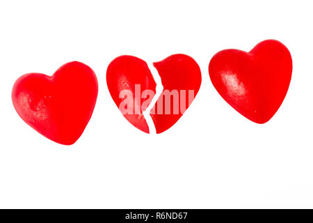 Broken heart or heartache concept with three bright red jelly heart shaped sweets next to each other with middle one cut in half isolated on white background - Stock Image