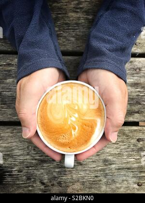 Looking down from above onto a a pair of male hands cupping a hot cup of cappuccino coffee on a wooden table - Stock Image