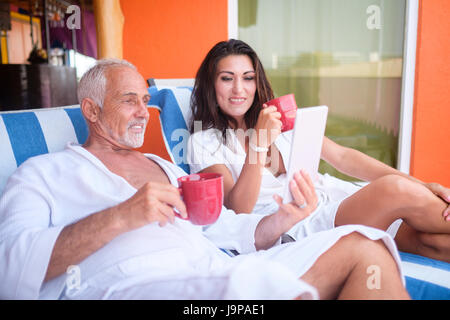 Older man and young woman using a tablet computer while enjoying coffee in bathrobes on loung chairs, Nuevo Vallarta, - Stock Image