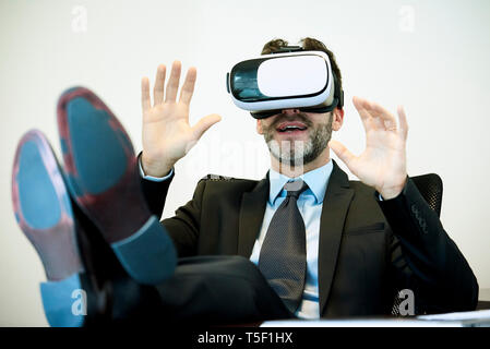 Businessman using virtual reality headset in office - Stock Image